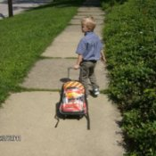 Small boy pulling a loaded sledge or similar wheeless conveyance down the sidewalk.