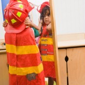 LIttle BOy Looking in the Mirror at his Fire Fighter Costume