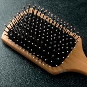 Wooden hairbrush on a black background.