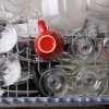 An open dishwasher full of clean dishes.