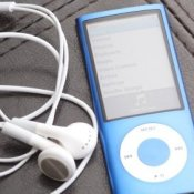 A blue iPod and earbuds on a black leather surface.