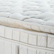 Up close photo of a pillow top mattress.