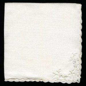 White linen napkin with embroidered corner.
