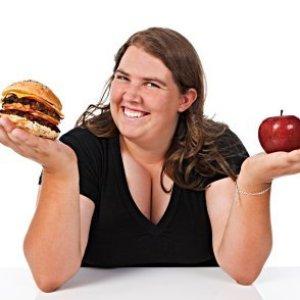 Woman choosing between an apple and a hamburger.