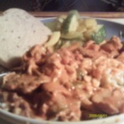 Plate of paprikash over spaetzle with a slice of rye bread.