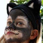 Girl with her has face painted like a black cat.