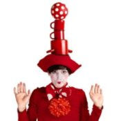 A clown dressed in red balancing cups on their head.