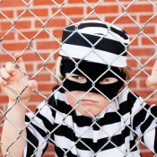 Boy Behind Fence in Convict Costume
