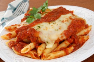 A plate of chicken parmesan on penne pasta, topped with tomato sauce and melted cheese.