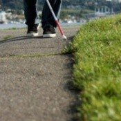 A blind man walking a path with a white cane.
