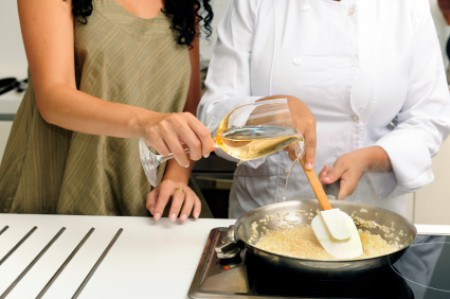 A woman pouring wine into a pan.