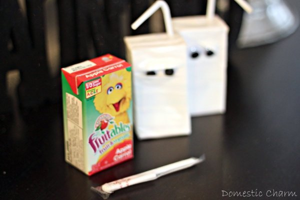 Three juice boxes, two decorated as mummies and one unadorned.