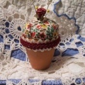 A pincushion made from fabric and a terra cotta pot.