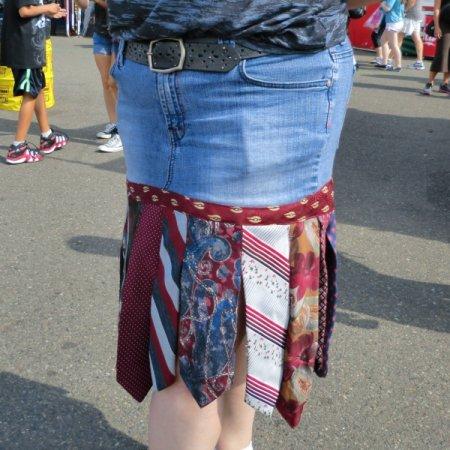 Upclose photo of necktie and denim skirt.