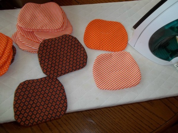 Several pumpkin shapes after sewing and turning. They are scattered on an ironing pad next to a steam iron.