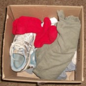 Emergency clothing and shoes in cardboard box.