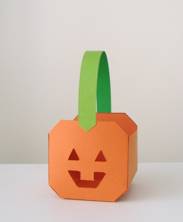 Small paper paper pumpkin basket. Pumpkin is orange, handle is green.