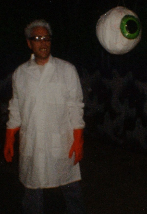 Mad scientist in a dark area with a fake eyeball hanging down.