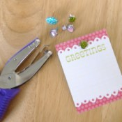 Hole punch, small card, and decorative brads.