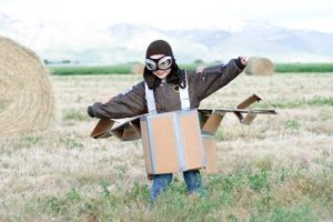 Young Boy Pretending to be a Pilot in Cardboard Plane