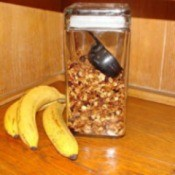 Container of homemade granola and three bananas.