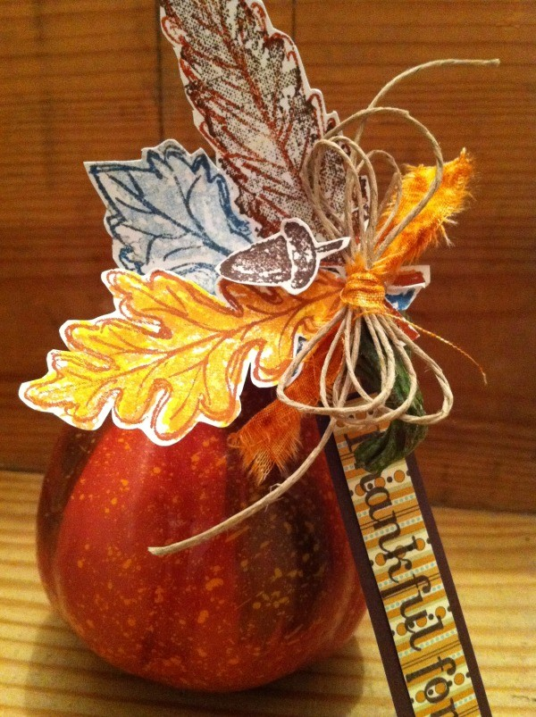 Speckled pumpkin or gourd with paper leaves, acorn, and raffia decorations.