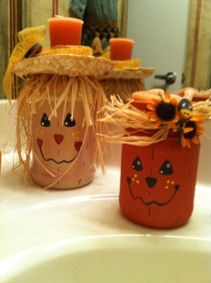 A scarecrow and a pumkin candle holder sitting on a sink.