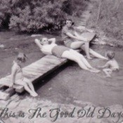 An old black and white photo of people swimming and sunning.