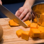 Photo of someone cutting up a pumpkin.
