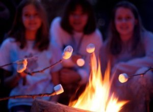 Girls roasting marshmallows over a campfire while camping.