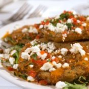A plate of fried green tomatoes with feta cheese garnish.