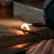 Photo of a jeweler heating a gold ring with a torch.