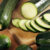 A cutting board with whole and sliced zucchini.