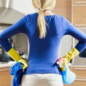 House Cleaning Tips, A woman with cleaning supplies after cleaning her kitchen.