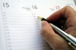 Picture of someone writing in a day planner.