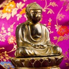 Brass Buddha figurine on floral fabric.