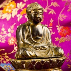 Brass Buddha figurine on floral fabric.