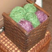 Finished basket storage, with balls of green and purple yarn artfully arranged on top.