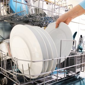 Someone loading dishes into a dishwasher.