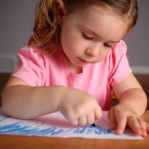 Little girl coloring with a blue crayon on a piece of paper.