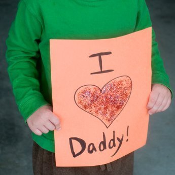 """Homemade Father's Day Gifts, A child holding a homemade card that says """"I love Daddy""""."""