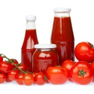 Fresh tomatoes surrounding three bottles of homemade ketchup.