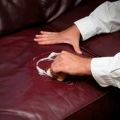 Man's hands cleaning a leather couch.