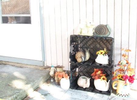 Decorative snails on plastic crates along with fall colored silk flowers.