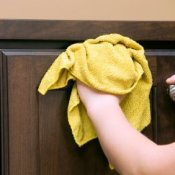 Homemade Kitchen Cabinet Degreaser Recipe, Rag in hand cleaning dark kitchen cabinet