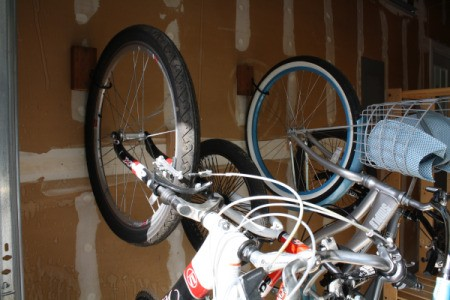 Two bikes hanging from J hooks.