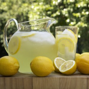 A pitcher of lemonade with a glass and some whole lemons.