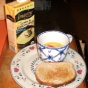 Cup of boxed soup and slice of toast. Box of soup in background.