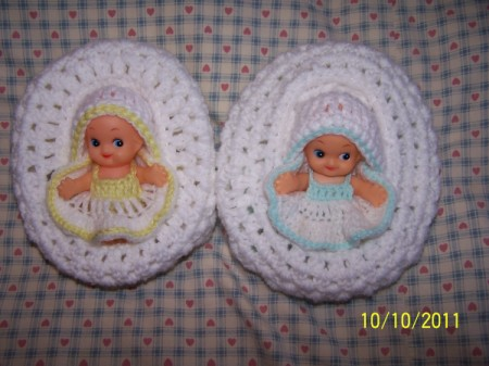 Two baby cradle church purses with Kewpie dolls inside.