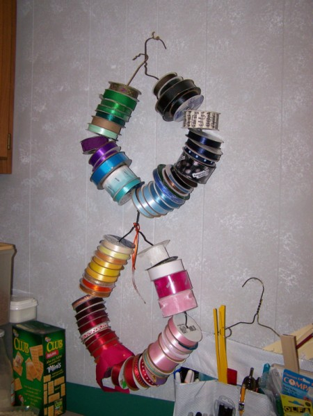 Rolls of ribbon on two wire hangers hanging on the wall.